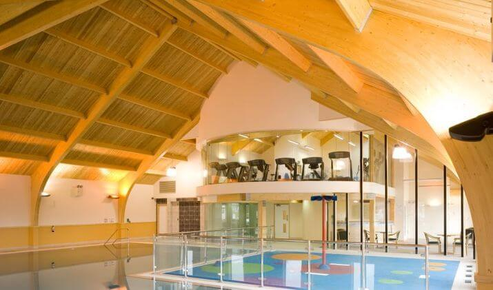 Interior view of indoor swimming pool and gym at Home Farm Holiday Park