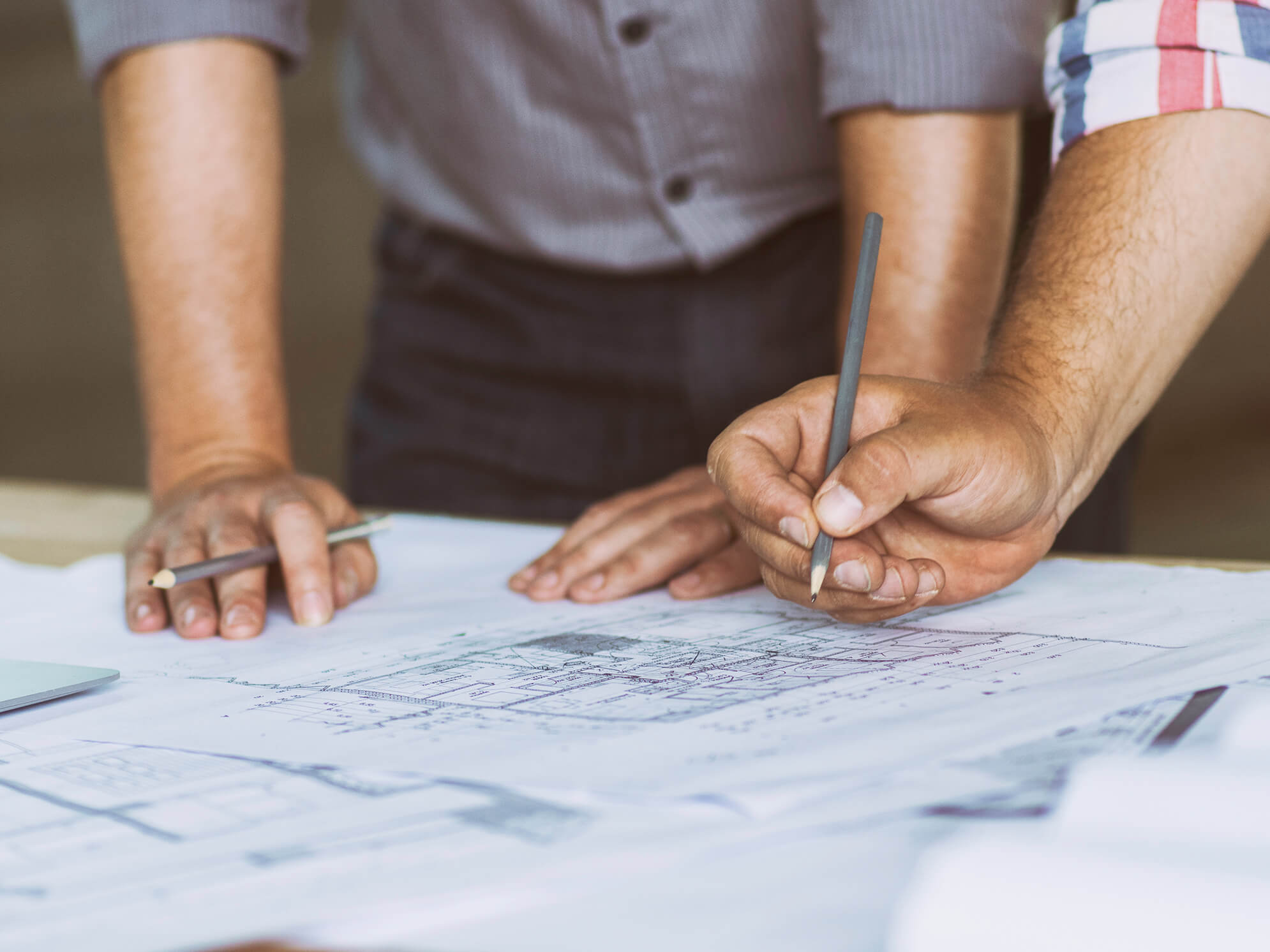 Close up of two peoples hand resting on an architects drawings